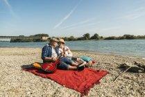 Senior pareja con guitarra en manta en la playa - foto de stock