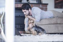 Man with dog lying on couch looking at laptop — Stock Photo