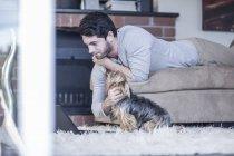 Человек с собакой лежит на диване и смотрит на ноутбук — стоковое фото