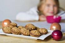 Bagattelle e piatto di biscotti fatti in casa con la ragazza sulla priorità bassa — Foto stock