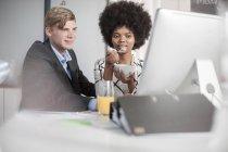 Dois colegas no escritório olhando para a tela do computador — Fotografia de Stock
