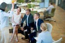 Молодий підприємець говорити з вагітні businessspeople в офісі — стокове фото