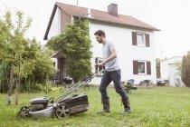 Взрослый кавказский мужчина стрижет газон — стоковое фото