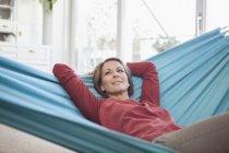 Lächelnde Frau zu Hause in Hängematte liegend — Stockfoto