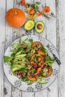 Autumnal salad with squash, pomegranate seeds, avocado and walnuts — Stock Photo
