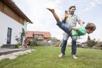Père de ludique s'amuser avec fils dans le jardin — Photo de stock