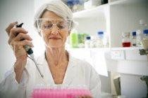 Женщина-профессор заполняет образцы в лаборатории — стоковое фото