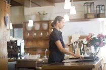 Waitress preparing bill at counter in restaurant — Stock Photo