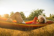 Smiling woman wearing hat relaxing in a hammock — Stock Photo