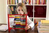 Portrait de jeune fille à l'aide d'abacus à table — Photo de stock
