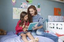 Мать и маленькая дочь сидят вместе на кровати в детской комнате и читают книгу — стоковое фото