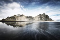 Исландия, Stokksnes, Вестрахорн горы, пляж Черный песок с камнями на заднем плане — стоковое фото