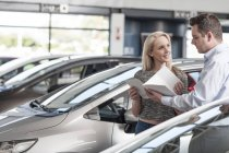 Car dealer explaining new car to young woman — Stock Photo