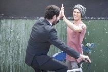 Молодой человек с высоким fiving скейтборд с бизнесменом на велосипеде — стоковое фото