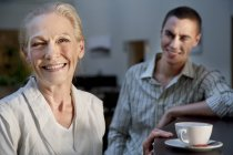 Portrait of smiling senior woman with cup of coffee and young man in background — Stock Photo