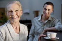 Retrato de sonriente mujer senior con taza de café y joven en fondo - foto de stock