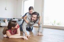 Famiglia felice sdraiata sul pavimento, giocando con la figlia — Foto stock