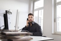 Caucasian man at desk in office talking on phone — Stock Photo