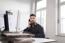 Homem caucasiano na mesa no escritório falando no telefone — Fotografia de Stock