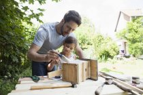 Caucasian father and daughter painting a birdhouse — Stock Photo