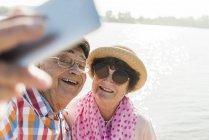 Пожилые супружеские пары, принимая selfie на Риверсайд — стоковое фото