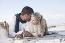 Couple lying on a blanket on beach and having picnic — Stock Photo