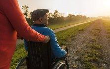 Старший жінка, штовхаючи чоловіка в інвалідному візку в природі — стокове фото