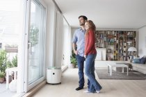 Couple in living room looking out of window — Stock Photo