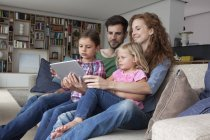 Couple sitting with their with two little daughters on couch in the living room looking at digital tablet — Stock Photo