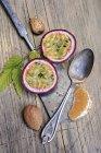 Fruta de la pasión en rodajas, rebanada de mandarina, almendras y cuchara de plata en madera - foto de stock