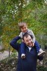 Kleiner Junge sitzt auf den Schultern der Väter lachen — Stockfoto