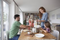 Couple with two children going to have lunch together at home — Stock Photo
