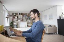 Homem caucasiano em casa usando laptop — Fotografia de Stock