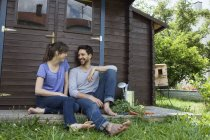 Smiling couple sitting at garden shed — Stock Photo