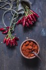 Bunches of red chili peppers and bowl with chili powder on wood — Stock Photo
