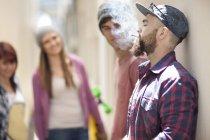 Giovane che fuma una sigaretta con amici a sfondo — Foto stock