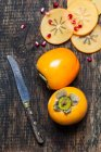 Kaki intero ed affettato con i semi di melograno e coltello su legno scuro — Foto stock