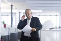 Businessman in open space office reading document — Stock Photo