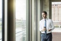 Retrato de hombre de negocios con café para llevar y smartphone mirando a través de la ventana - foto de stock
