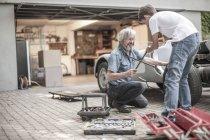 Abuelo y nieto restaurando un coche juntos - foto de stock