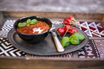 Bowl of homemade tomato soup with chilli threads on wood — Stock Photo