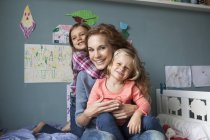 Portrait of woman with her little daughters in children's room — Stock Photo