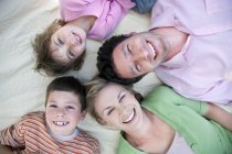 Group picture of happy family lying together on blanket — Stock Photo