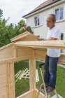 Man setting up a garden shed — Stock Photo