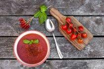 Bol de soupe de tomate maison avec fils de piment sur bois — Photo de stock