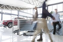 Three people walking in car dealership — Stock Photo