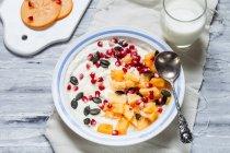 Dish of natural yogurt, kaki, pomegranate seeds, almond and pumpkin seeds — Stock Photo