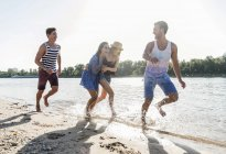 Happy friends running and laughing at the river — Stock Photo