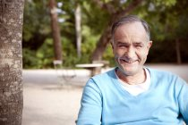 Portrait of smiling mature man sitting in the garden — Stock Photo