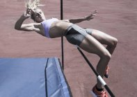 Female athlete high jumping — Stock Photo